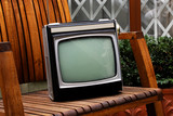 Retro TV as obsolete dusty TV receiver laid on wooden chair outside - 243710382