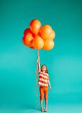Cute girl holding orange balloons - 243710947
