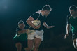 Rugby player running with ball and tackling