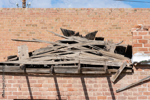 Brick wall and collapsed roof of an abandoned building - 243724763