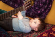 baby is making music with a guitar at home