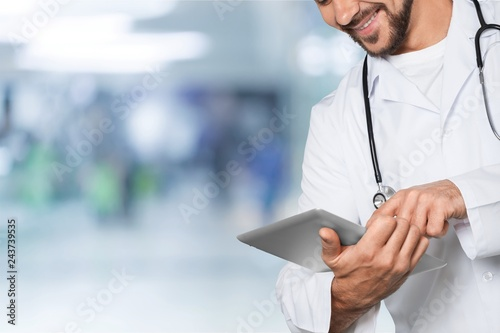 Leinwanddruck Bild Attractive young female doctor with blurred hospital interior on