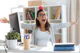 Happy young business woman having fun and holding red apple over her head in the office. - 243744786