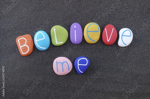 Believe me, motivational words composed with colored stones over black sand