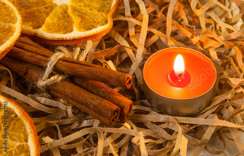 Orange slice and fragrant cinnamon sticks with a red burning candle