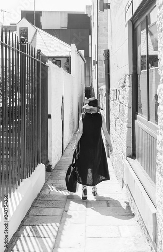 fototapeta na ścianę Rear view of woman in black hat and dress walking in alley way (black and white)