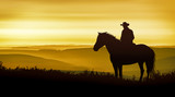 Fototapeta Konie - A cowboy on horseback observes the golden mountains © ginettigino