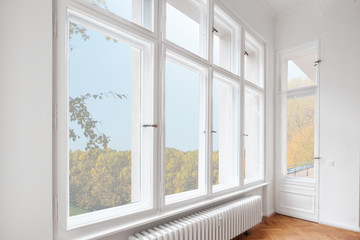 big wooden windows in apartment room of old building