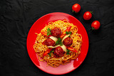 Italian pasta with tomato sauce and meatballs in a red plate, dark background