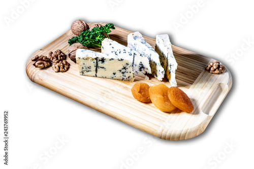 Some peaces of the cheese blue mold roquefort  with dried apricot and peaces of the nuts with parsley at the wooden desk and background