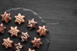 Leinwandbild Motiv Star-shaped chocolates on dark textured background, copy-space