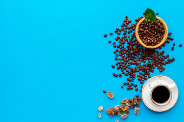 Brown roasted coffee beans scattered on blue background and cup of americano top view mockup © 9dreamstudio