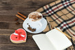 Cup of cappuccino, heart shaped cookies width message, notebook and checkered plaid on a brown wooden table