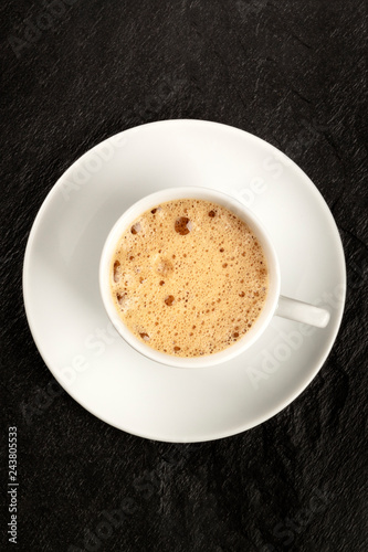 An overhead photo of a cup of coffee with foam on a black background with copy space