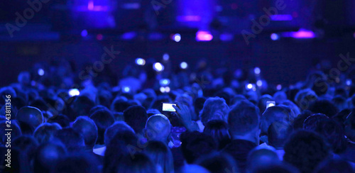 many people with modern mobile phone at live concert