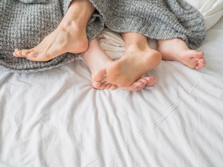 Close up of the feet of a couple on the bed. Loving couple is lying on bed under blanket. Relationships concept. © Stavros