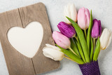 Fototapeta Tulipany - Fresh colorful tulips and heart shaped frame © ffphoto