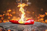 Feurig scharfe Chilischote mit Flamme