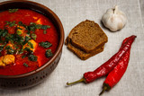 Stew in a clay bowl with garlic, bread and pepper on sackcloth - 243834189