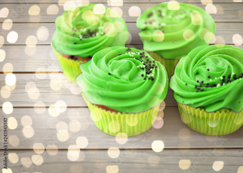 food, st patricks day and pastry concept - close up of cupcakes or muffins with green buttercream frosting and sprinkles on wooden background and festive lights