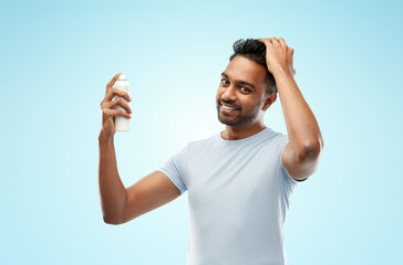 grooming, hairstyling and people concept - happy smiling indian man applying hair spray over blue background © Syda Productions