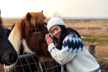 Woman cuddling with Icelandic horse on Iceland road trip © creativefamily