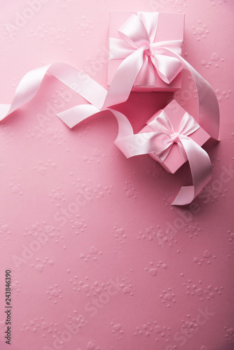 Valentine's Day. Pink gifts, presents tied with rosy ribbon on pink heart shape patterned background top view. Valentines Day, 8 March, Women's Day, Birthday, Mother's Day holiday background
