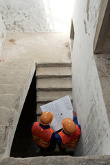 Civil engineers analyzing construction plan when walking up the stairs, view from above © DragonImages