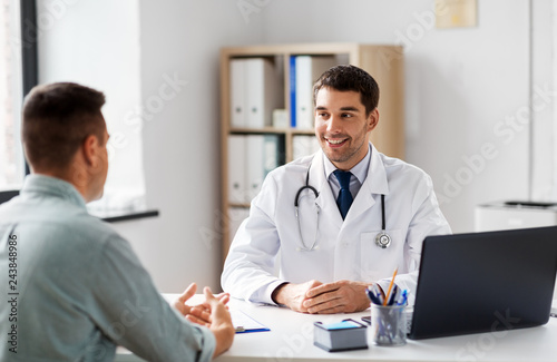 medicine, healthcare and people concept - smiling doctor talking to male patient at medical office in hospital - 243848986