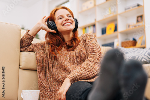 Woman relaxing at home with headphones - 243850915