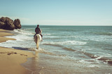 Fototapeta Konie - young man ride a white horse on the beach © puckillustrations