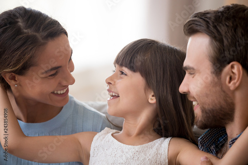 Leinwandbild Motiv Cute little daughter looking at dad laughing having fun talking to parents, smiling adorable child girl enjoying loving family of three good sincere communication, kid and father warm relationships