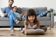 Leinwandbild Motiv Cute adorable little girl enjoying reading fairytale laughing lying on warm floor relaxing at home with parents, happy kid daughter having fun holding book in living room, creative child activity