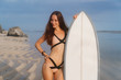 Attractive girl with long hair in swimsuit standing with surfboard on tropical beach