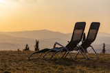Two empty chaise lounges on a grass overlooking the hills of Tuscany in evening light, Italy - 243870962