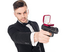male killer in black suit aiming with gun with proposal ring, isolated on white