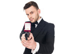 handsome secret agent in black suit aiming with handgun with proposal ring, isolated on white