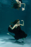 Hot Slim Elegant Woman Posing Under water in beautiful long dress alone in the deep - 243880580