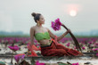 Traditional asian woman harvest red lotus flower in nature river, Thailand