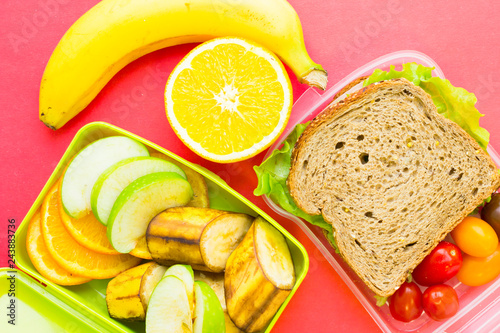 Leinwandbild Motiv School lunch box. Bread, orange, baby corns, carrot and tomatoes in green plastic container