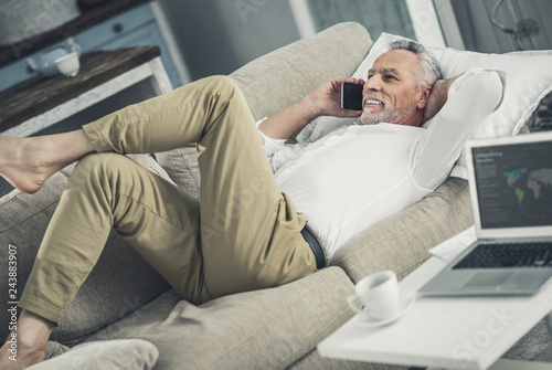 Wall mural Businessman relaxing while lying on sofa