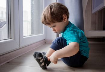 little toddler boy sitting on floor near window and looking at foots © Masson