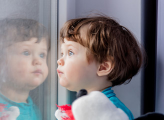 a little boy is standing by the window and looking into it, dreaming © Masson