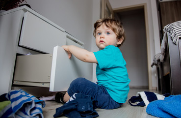 Little toddler boy play with clothes from cupboard at home © Masson