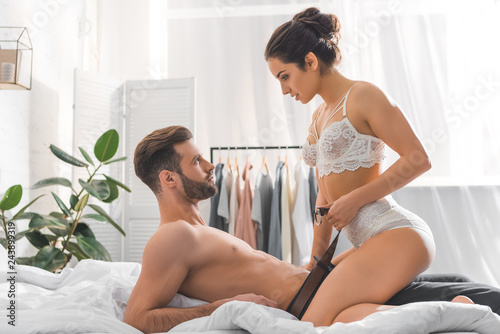 Leinwandbild Motiv beautiful sexy woman in white lingerie undressing man during foreplay in bedroom