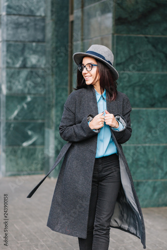 e4b2284ed407 Stylish city portrait fashionable young woman walking in long grey coat on  street. Wearing hat