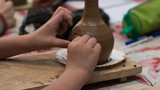 child in the process of decorating the clay pot. children's pottery studio - 243904519