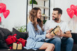 loving couple gifting presents in room with heart-shaped balloons