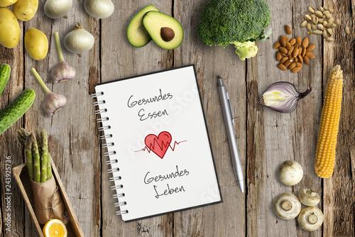 """Leinwandbild Motiv gesunde Lebensmittel und Notizblock mit Aufschrift """"Gesundes Essen, Gesundes Leben"""" auf Holzuntergrund"""