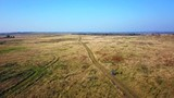 Aerial view of a man cycling at path in a meadow - 243944171